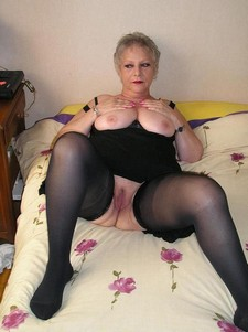Blonde old woman in black bra and stickings