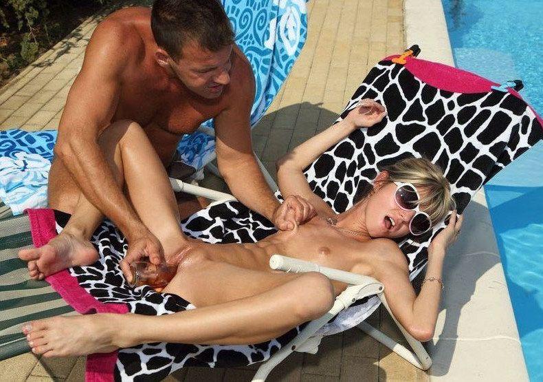A guy caresses a gf near the pool
