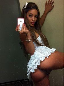 Sexy brunette latina taking selfshot in white lingerie.