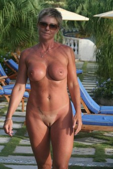 Mature woman posing nude on the beach: showing her great tits and exciting shaven pussy..