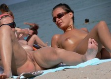 Sexy white chick tanning her unsuspecting pussy on a beach, creating the opportunity for..