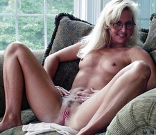 Blonde milf with small tits showing her pussy on couch.