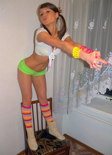 Cute girl in pigtails, bright green short shorts, and neon stripy socks.